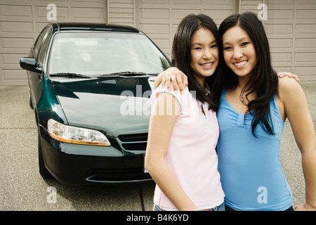 Asian sisters hugging in driveway Banque D'Images