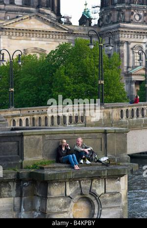 Un couple assis sur le pont Bodestrasse, Berlin, Allemagne Banque D'Images