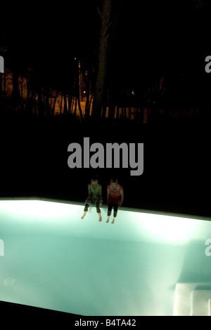 Deux femmes à la recherche vers le bas s'asseoir sur le bord de la lumière jusqu'piscine la nuit avec leurs pieds Banque D'Images