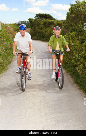 Senior couple cycling on country lane Banque D'Images