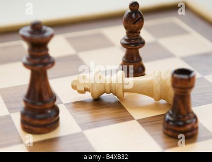 Pièces des échecs entourant fallen king