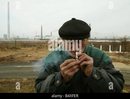 Copsa Mica Roumanie Novembre 2006 Copsa Mica plus polluées d'Europe, Prêt Butuzean place allume sa cigarette en Banque D'Images