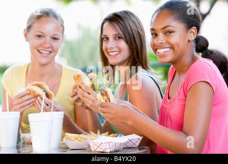 Teenage Girls Sitting Outdoors Eating Fast Food Banque D'Images