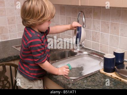 Bébé garçon enfant de l'évier de la cuisine en faisant la vaisselle avec eau chaude robinet ouvert Banque D'Images