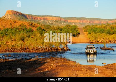 Traversée de la rivière Pentecôte SUV avec Cockburn s'étend en arrière-plan, Gibb River Road, Kimberley, Western Banque D'Images