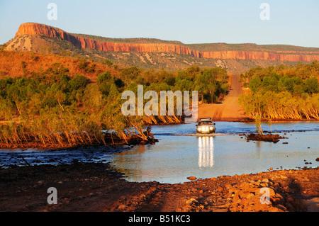 Passage du véhicule avec la rivière Pentecôte Cockburn s'étend en arrière-plan, Gibb River Road, Kimberley, Australie Banque D'Images