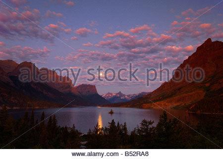 La pleine lune se couche sur le lac de Sainte Marie comme la première lumière du jour rougit le ciel de Glacier Banque D'Images