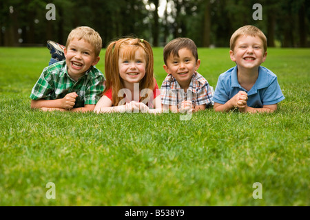 Enfants laying in grass in park Banque D'Images