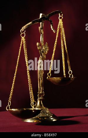 Les échelles de la justice en laiton déséquilibrée vide isolé sur fond rouge foncé Banque D'Images