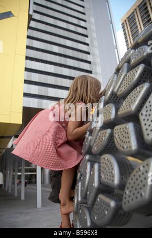 Jeune fille enfant grimper sur l'extérieur de la sculpture moderne nouveau Square Brisbane City Council Building Banque D'Images