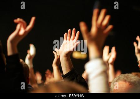 Fans lèvent la main lors d'un concert Banque D'Images