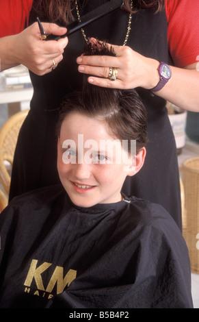 Jeune garçon à coiffeurs faisant couper les cheveux Banque D'Images