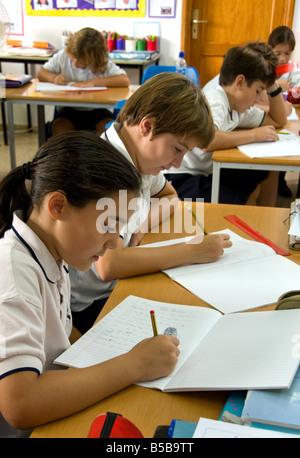 Les enfants de l'école junior se concentrer sur leur examen écrit à l'école de la classe 24 en classe Banque D'Images