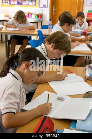 Les enfants de l'école junior 9-11 ans se concentrer sur leur examen écrit à un bureau de classe en classe de l'école Banque D'Images