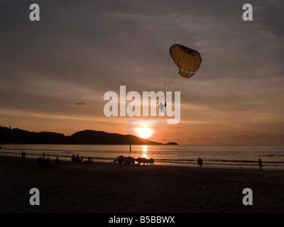 La motomarine qui se profile au-dessus de la plage au coucher du soleil à Phuket Thaïlande