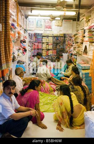 Les femmes shopping et l'achat d'un sari saris en boutique dans le marché Kinari, Old Delhi Inde Banque D'Images