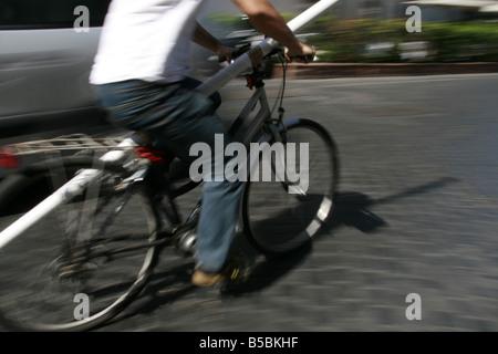 Homme portant de long tube blanc sur vélo en ville dans la rue Ville Banque D'Images