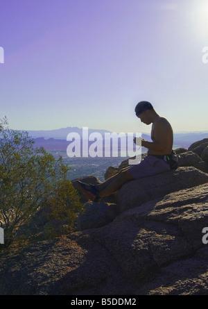 Randonneur Alpiniste avec Sun reposant à pic de Camelback Mountain, Phoenix, Arizona, USA Banque D'Images