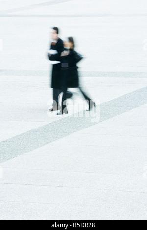 Businessman and businesswoman walking ensemble en place publique Banque D'Images