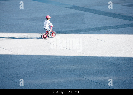 Child riding bicycle alone in public square Banque D'Images