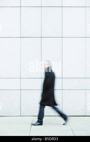Businessman walking alone les mains dans les poches vers le bas trottoir