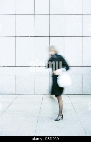 Businesswoman talking on phone tout en descendant un trottoir Banque D'Images