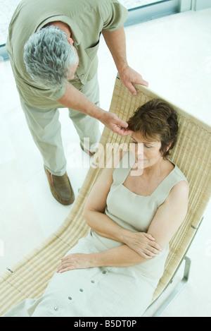 Woman relaxing on lounge chair, mari se pencher pour toucher ses cheveux Banque D'Images