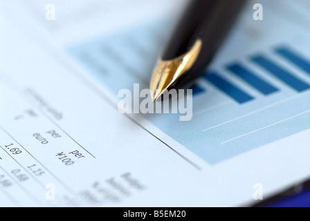 Stylo d'or sur le tableau financier