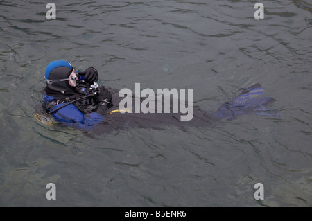 Scuba Diver flottant à la surface de l'eau sur le dos de l'équipement de contrôle Banque D'Images