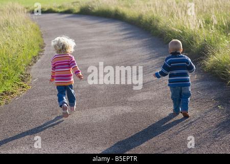 Little girl (2-3) and boy (1-2) en travers de chemin, vue arrière
