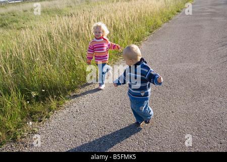 Little girl (2-3) and boy (1-2) à travers l'chemin