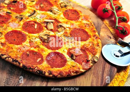 Pizza au pepperoni fraîchement cuit sur planche de bois Banque D'Images