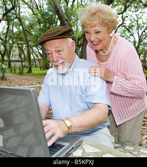 Couple sur ordinateur bénéficiant d'e mail de leurs petits-enfants Banque D'Images