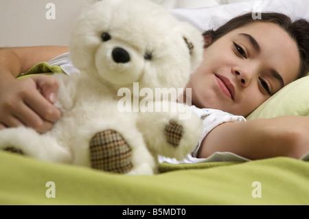 Une petite fille au lit holding a teddy bear Banque D'Images