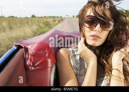 Une jeune femme assise sur le siège arrière d'une automobile Banque D'Images