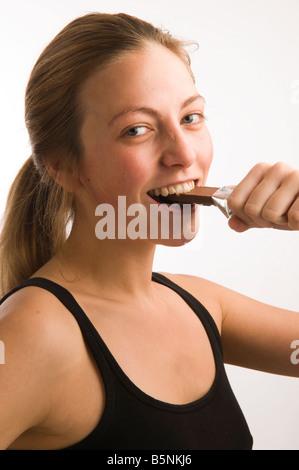 Santé de la jeune fille aux cheveux blond Caucasian woman Taking a bite out d'une barre de chocolat après l'exercice Banque D'Images