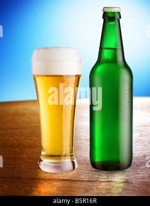 Bouteille en verre avec de la bière et se tenir sur une table sur un fond bleu Banque D'Images