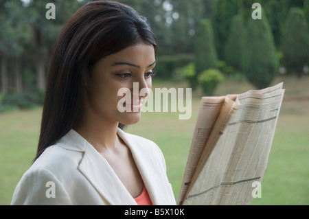 Businesswoman reading a newspaper Banque D'Images