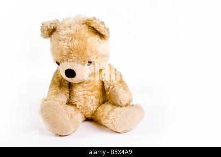 Vieux ours en peluche jaune avec une grosse tête à la triste sur fond blanc Banque D'Images