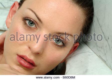 Jeune femme dans une baignoire face seul adultes fermer les yeux Banque D'Images