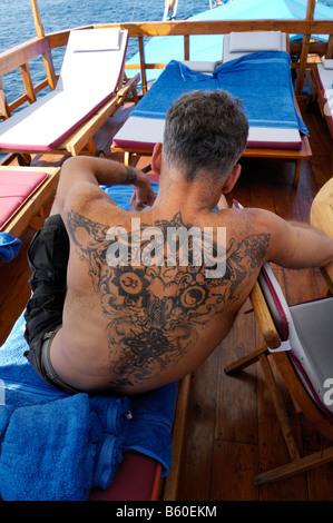 L'homme tatoué fortement de vous détendre sur la terrasse de la MS-Felicia, le Parc National de Komodo, Site du Banque D'Images