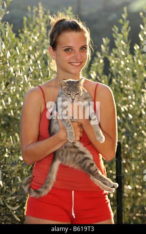 Jeune chat tigré gris étant détenu par une fille