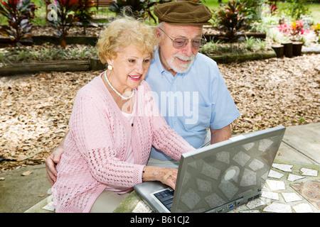 Couple à l'extérieur sur leur ordinateur portable Banque D'Images