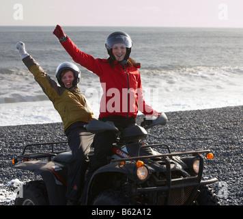 Les filles sur Quad équitation plage rocheuse de sable noir, l'Est de l'Islande, fjord Hornafjordur Banque D'Images