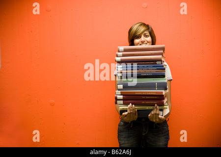 Dark-haired young female student holding une pile de livres alors qu'il se tenait devant un mur rouge-orange Banque D'Images