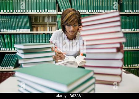 Jeune femme brune student sitting et la lecture avec de nombreux livres à la table en face d'une étagère dans une Banque D'Images