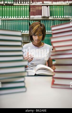 Dark-haired young female student sitting avec de nombreux livres à la table en face d'une étagère dans une bibliothèque Banque D'Images