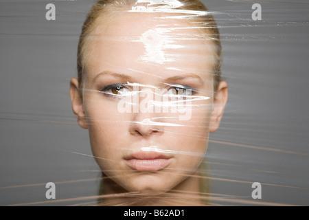 Young woman's face derrière une feuille de Ziploc®, symbolique pour l'éternelle jeunesse