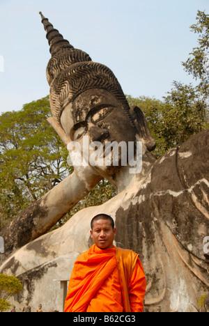 Le moine bouddhiste portant une robe orange en face d'une statue de Bouddha, Bouddha, Parc Suan Xieng Khuan, près Banque D'Images