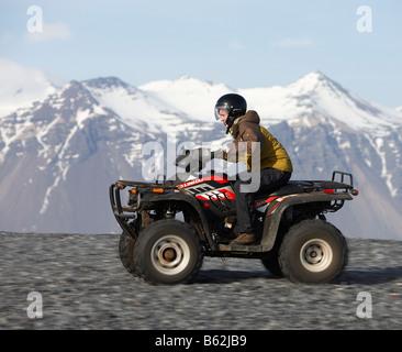 Girl riding Quad sur sable noir plage rocheuse, Hornafjordur, fjord Islande de l'Est